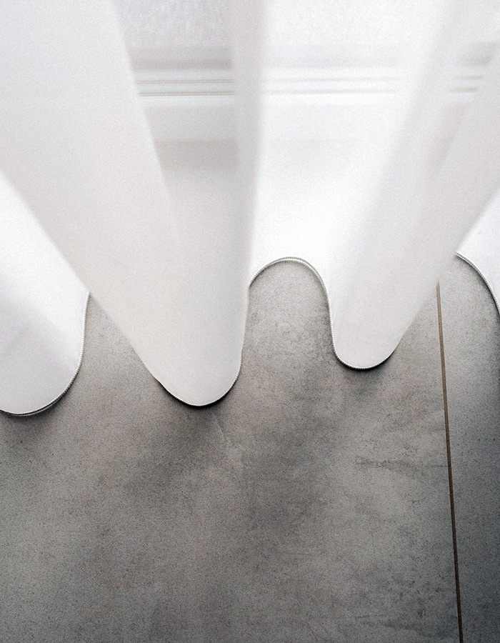 Gładkie woalowe firany i szara, betonowa podłoga