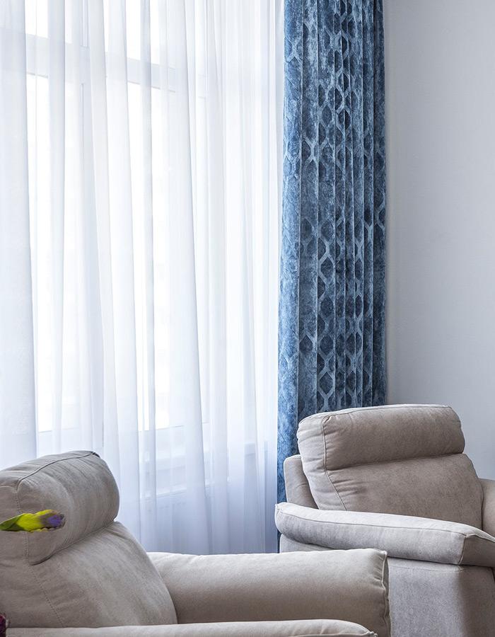 Woalowe firany i niebieskie zasłony we wzorki w salonie