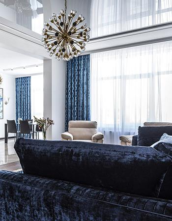 Napinany sufit, tapicerowane meble i białe firany w salonie w stylu glamour