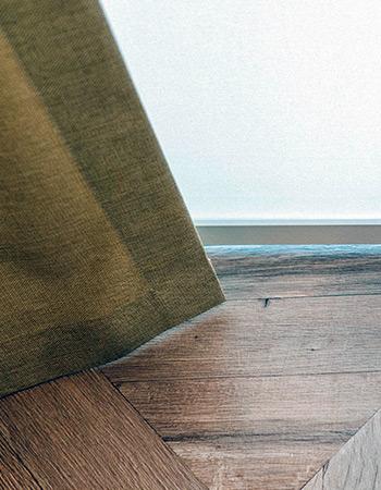 Kontrast drewnianej podłogi a także żółtej zasłony i białej przezroczystej rolety zwijanej