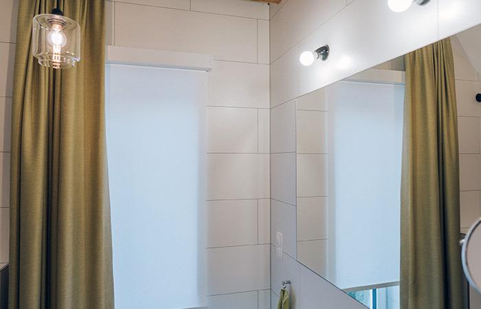 Żółte zasłony wraz r roletami zwijanymi w jasnej łazience