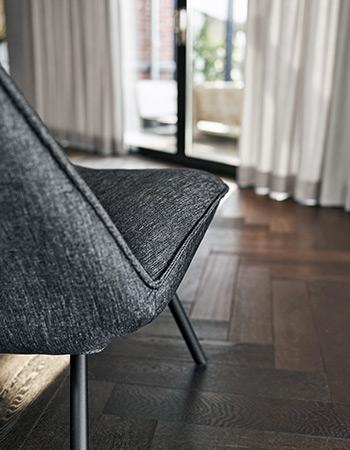 Drewniana podłoga, nowoczesny fotel na oknie szare zasłony