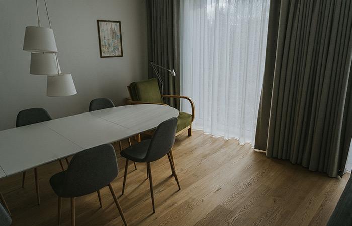 Zielony fotel, biały stół, drewniana podłoga a także szare zasłony wraz z firnami